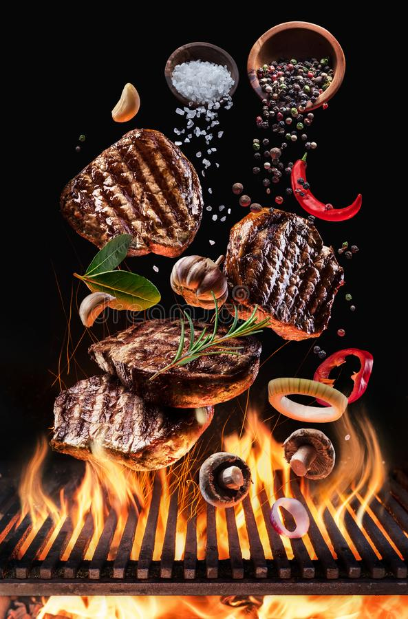 Cooked beef steaks with vegetables and spices fly over the blazing grill barbecue fire. Concept of flying food royalty free stock image