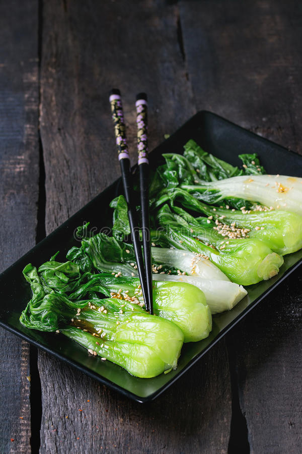 Cooked bok choy with sesame seeds. And chili pepper olive oil in black square ceramic plate with black chopsticks over old wooden table. Rustic style stock images
