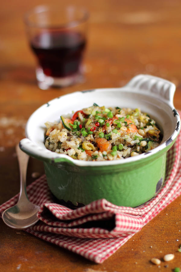 Cooked brown rice with celery, tomatoes and shrimps. In a pot royalty free stock photography