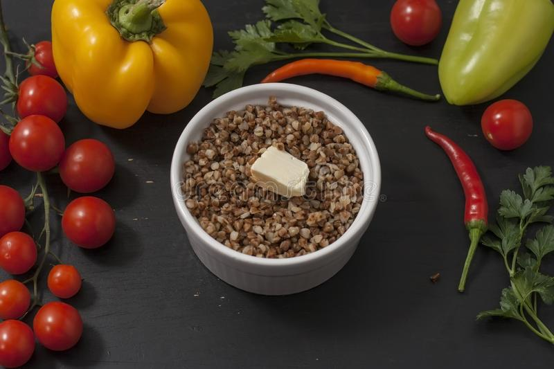 Cooked buckwheat porridge in a deep plate on a black wooden background with vegetables. royalty free stock photo