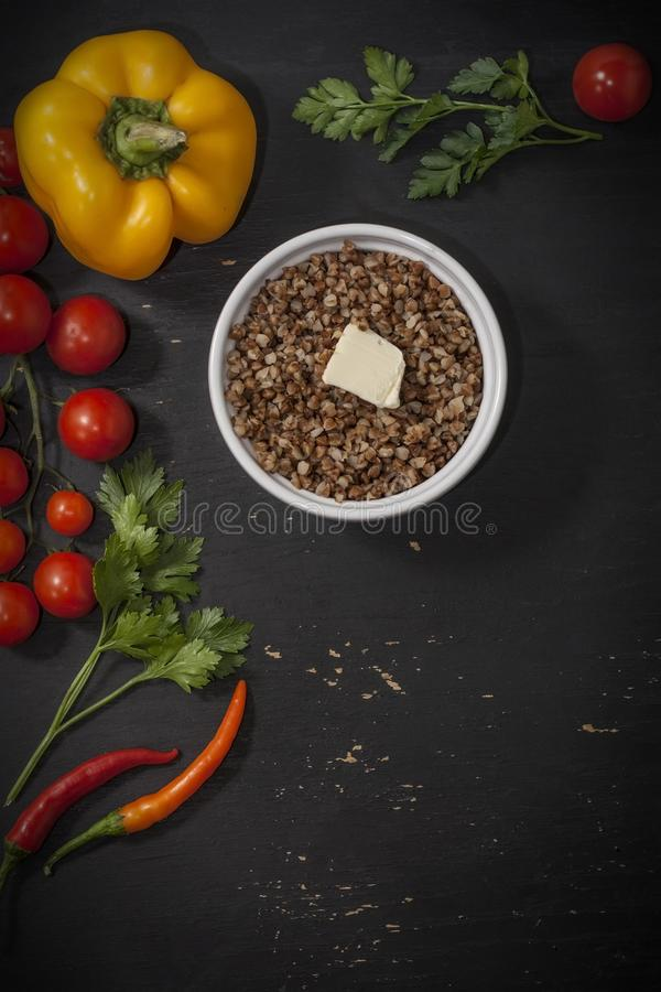 Cooked buckwheat porridge in a deep plate on a black wooden background with vegetables. Copy space. Top view stock photo
