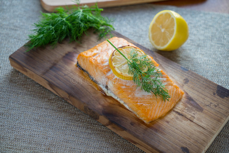 Cooked Cedar Plank Salmon. Fresh salmon on cedar plank with dill and lemon royalty free stock images