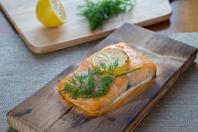 Cooked Cedar Plank Salmon. Fresh salmon on cedar plank with dill and lemon stock photography