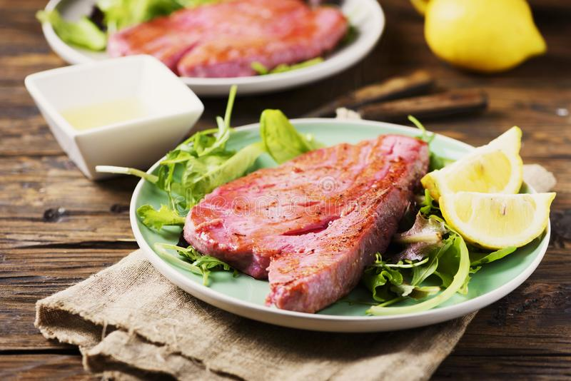 Cooked delicious tuna fish with green salad. Selective focus stock image
