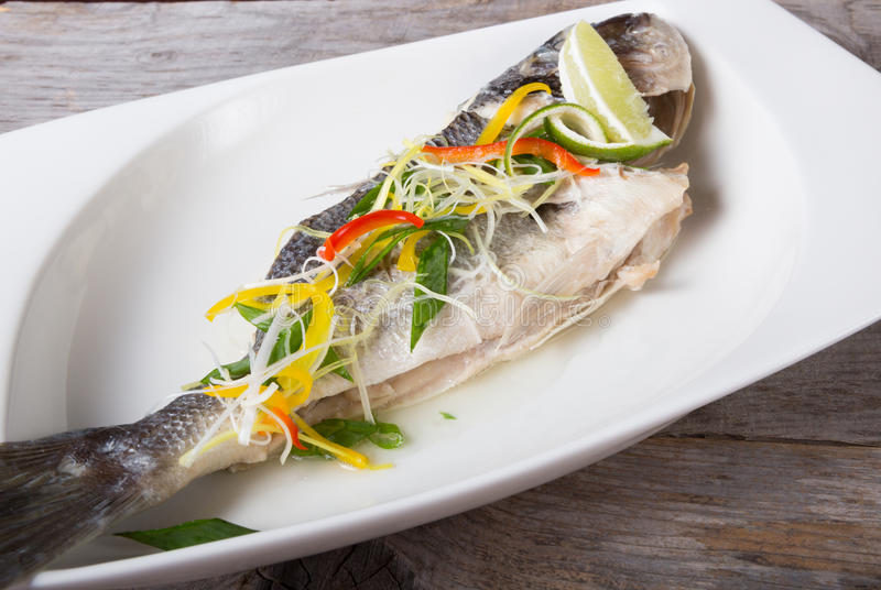 Cooked dorado fish. Served on a white plate with herbs stock images