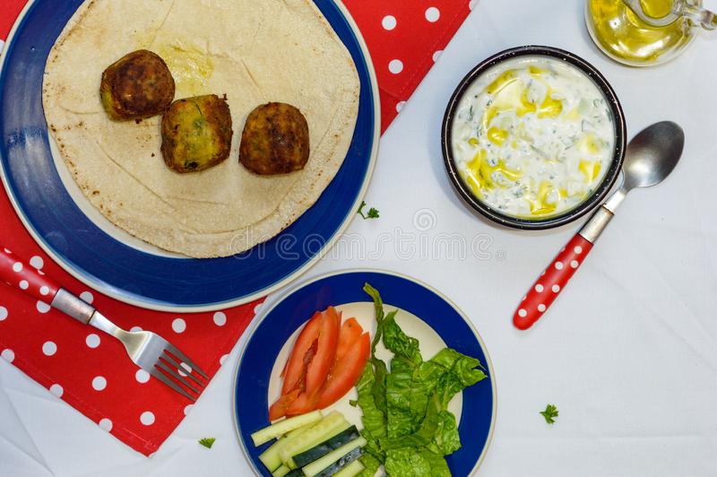 Cooked falafel on table with vegetables and yogurt sauce stock photos