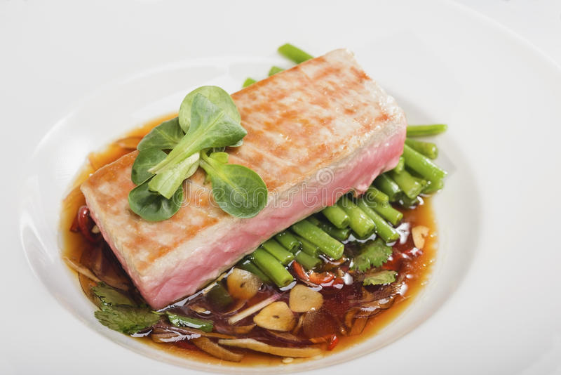 Cooked fish. In a plate decorated with verdure stock photo