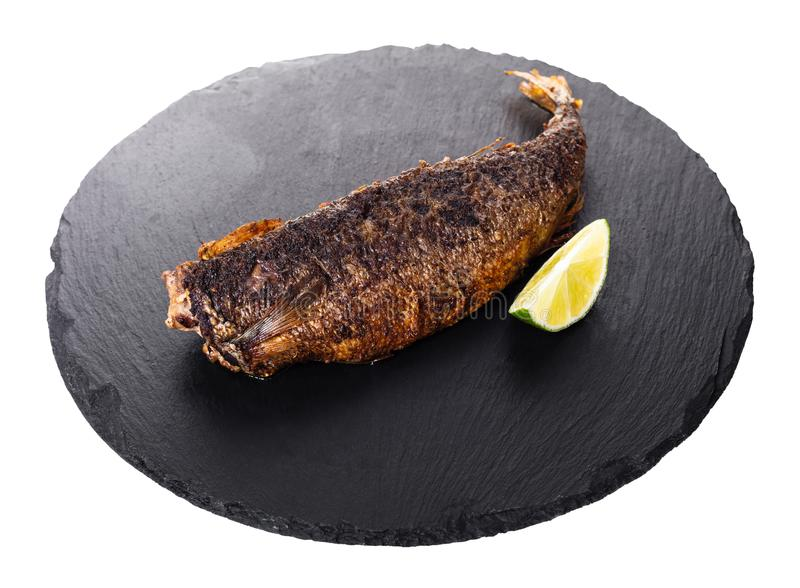 Cooked fish and a slice of lime. On white isolated background stock image
