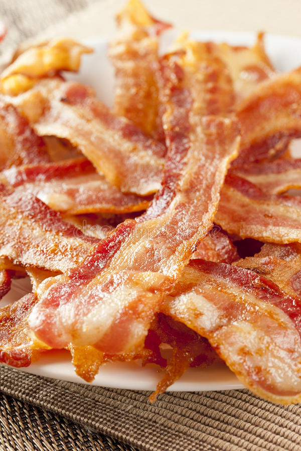 Cooked Greasy Bacon. Against a back ground stock photography