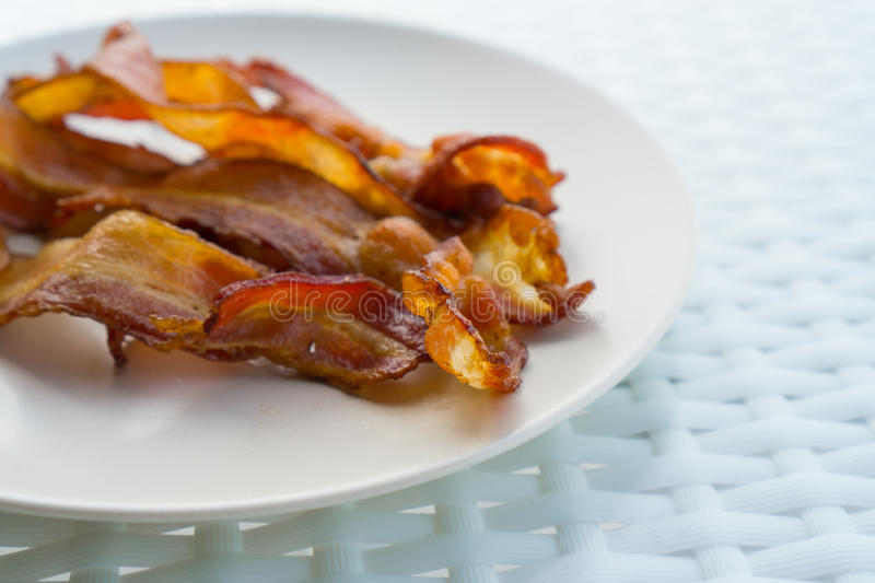 Cooked Greasy Bacon. On white plate royalty free stock photo