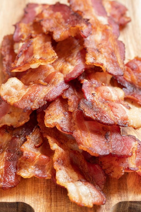 Cooked Greasy Bacon. On a wood board stock photography