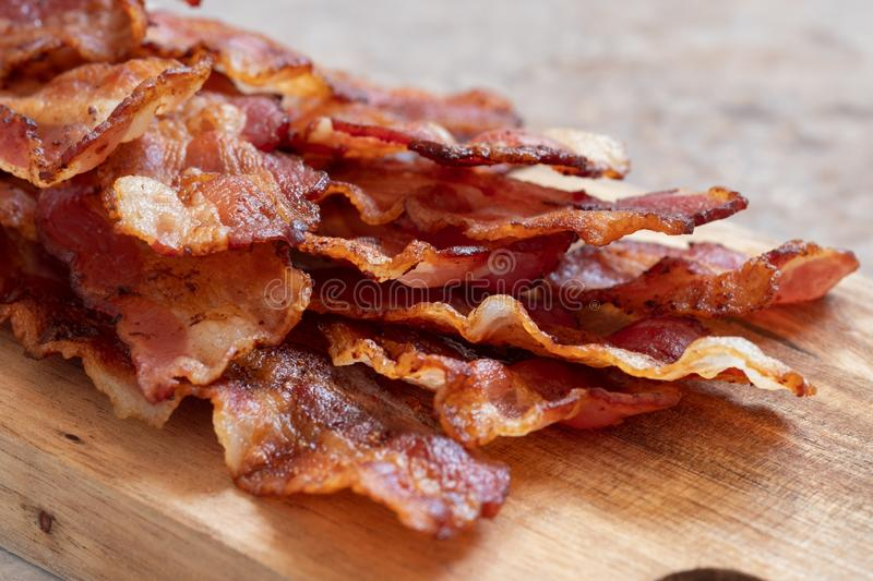 Cooked Greasy Bacon. On a wood board royalty free stock photos