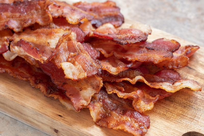 Cooked Greasy Bacon. On a wood board royalty free stock photo