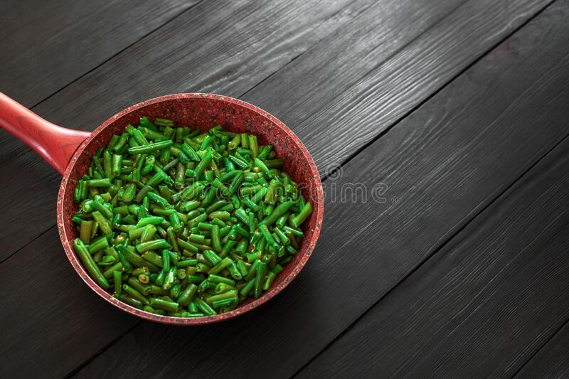 Cooked green beans in a frying pan on a black wooden background. Space to copy. Top view. Vegetable, vegetarian, food, healthy, dish, meal, fried, tasty stock photos