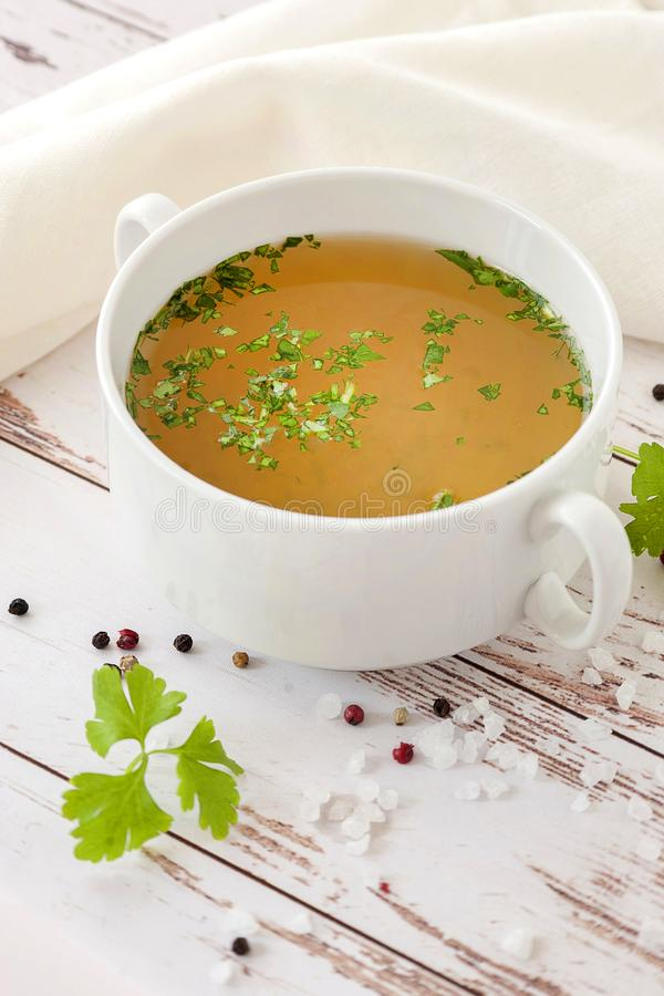 Cooked hot bone broth. With spices and fresh herbs. Medical dietary broth and superfood. For ketogenic diet and paleo diet. Serve on an individual plate on a stock photos