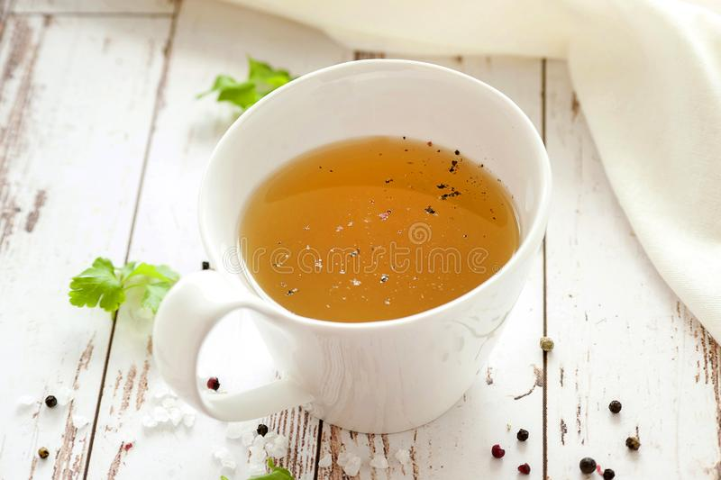 Cooked hot bone broth. With spices and fresh herbs. Medical dietary broth and superfood. For ketogenic diet and paleo diet. Serve on an individual plate on a royalty free stock photo