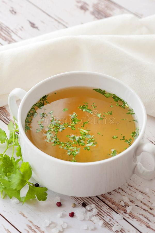 Cooked hot bone broth. With spices and fresh herbs. Medical dietary broth and superfood. For ketogenic diet and paleo diet. Serve on an individual plate on a royalty free stock photography
