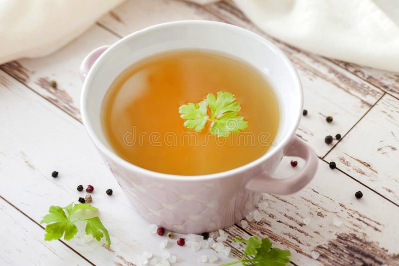 Bone broth. Cooked hot bone broth with spices and fresh herbs. Medical dietary broth and superfood. For ketogenic diet and paleo diet. Serve on an individual stock image