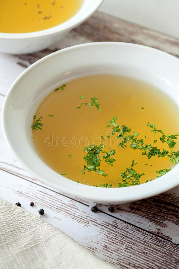 Cooked hot bone broth. With spices and fresh herbs. Medical dietary broth and superfood. For ketogenic diet and paleo diet. Serve on an individual plate on a stock photo