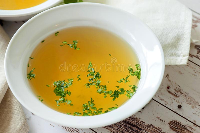 Cooked hot bone broth. With spices and fresh herbs. Medical dietary broth and superfood. For ketogenic diet and paleo diet. Serve on an individual plate on a royalty free stock photos