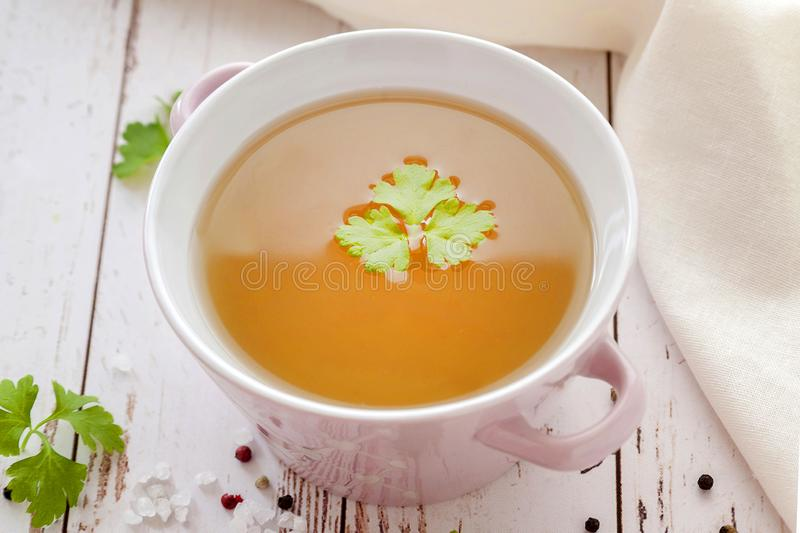 Bone broth. Cooked hot bone broth with spices and fresh herbs. Medical dietary broth and superfood. For ketogenic diet and paleo diet. Serve on an individual royalty free stock images
