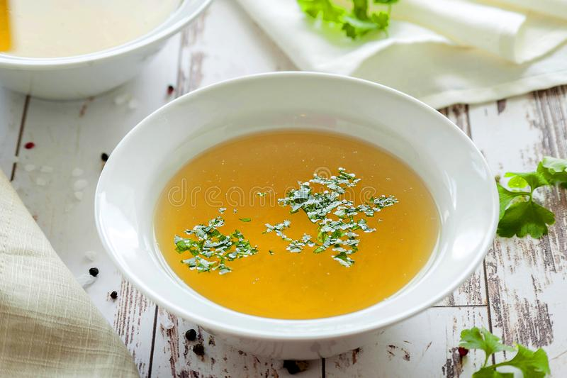 Hot bone broth. Cooked hot bone broth with spices and fresh herbs. Medical dietary broth and superfood. For ketogenic diet and paleo diet. Serve on an individual stock images