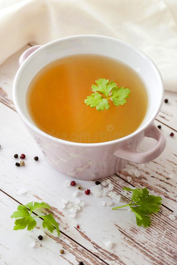 Cooked hot bone broth. With spices and fresh herbs. Medical dietary broth and superfood. For ketogenic diet and paleo diet. Serve on an individual plate on a stock photography