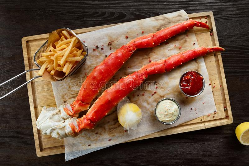 Cooked king crab legs with sauces and french fries royalty free stock photography