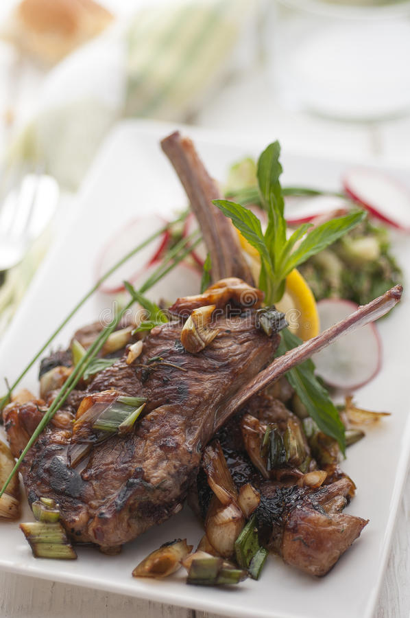 Cooked lamb chops. Garnished with fresh herbs royalty free stock photography