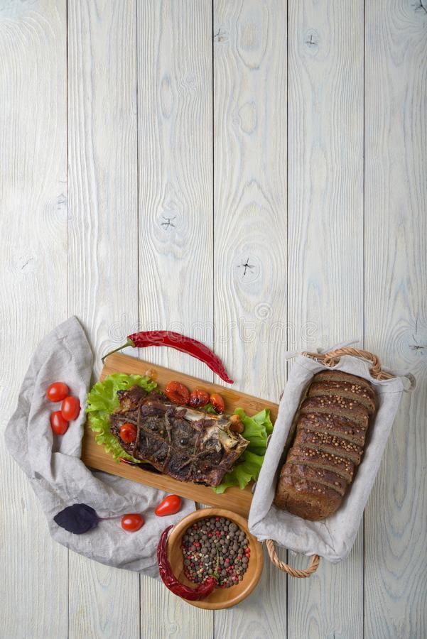 Cooked meat with ingredients. On a wooden background royalty free stock photo