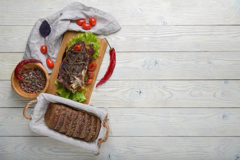 Cooked meat with ingredients. On a wooden background stock photo