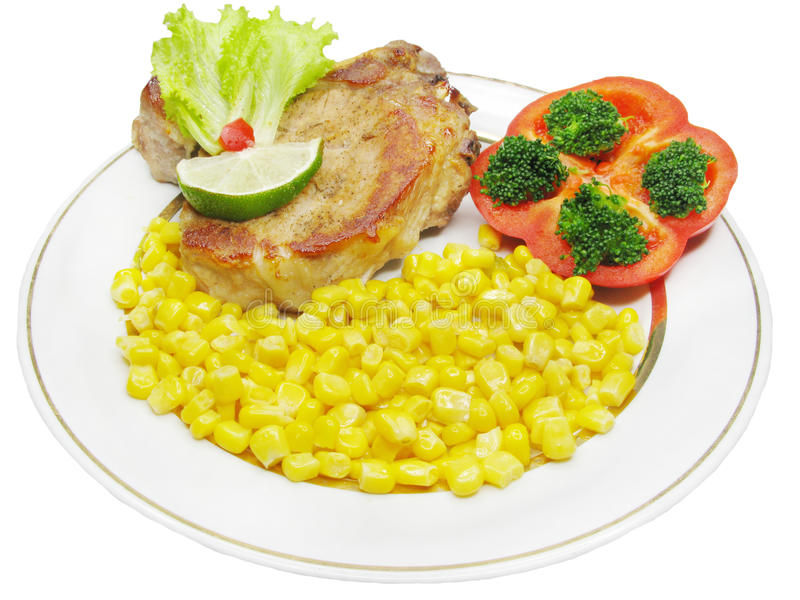 Cooked meat with vegetables. Cooked meat with corn and tomato royalty free stock photo