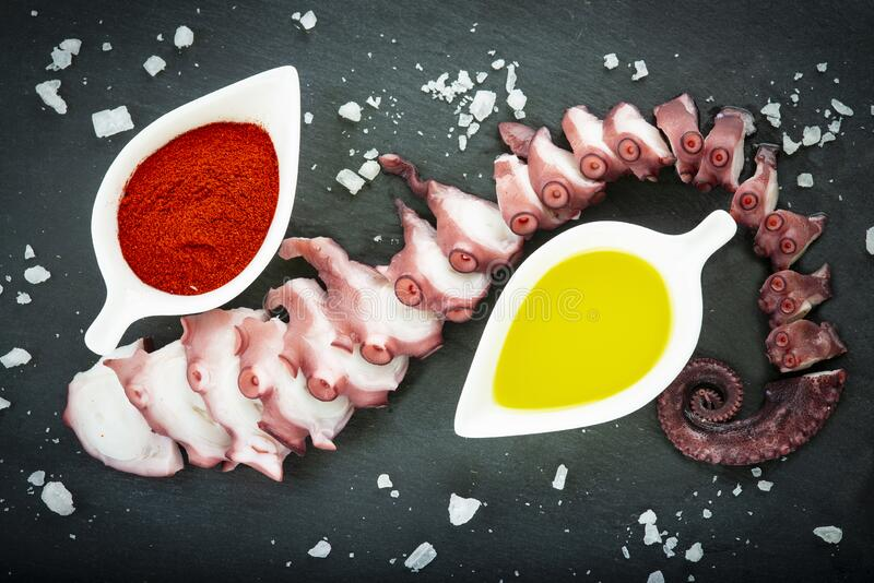 Cooked octopus over a slate plate decorated royalty free stock photo
