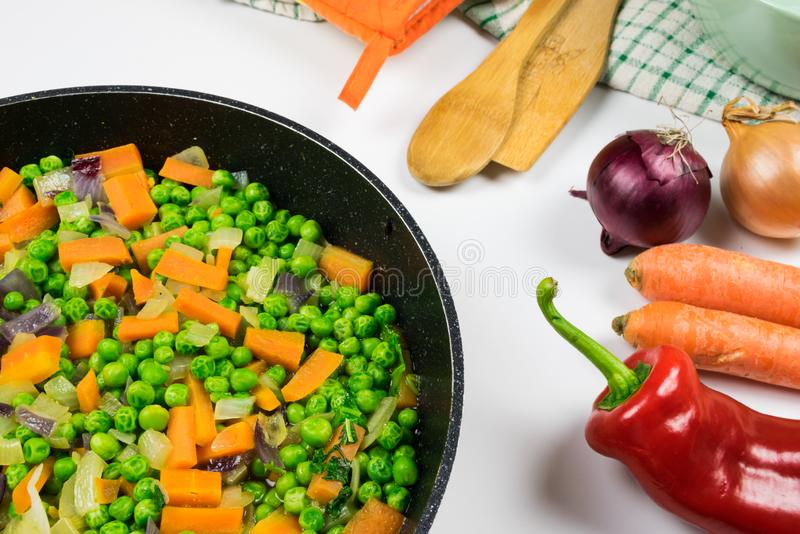 Cooked peas with carrot and onion in black pan on white table and raw vegetable, dish towel and spatula next to it. royalty free stock images