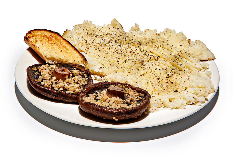 Cooked Portabella with garlic and baked potato. A plate with Cooked Portabella mushrooms with garlic and baked potato stock image