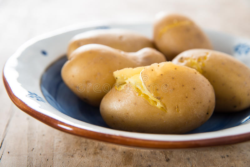 Cooked potatoes on hand painted terracotta dish royalty free stock photography