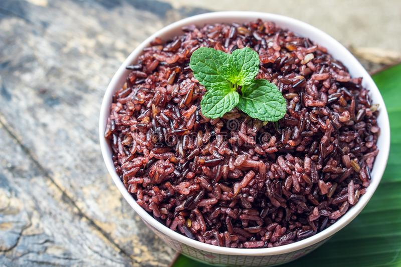 Cooked purple rice berry in bowl over green leaf background stock image
