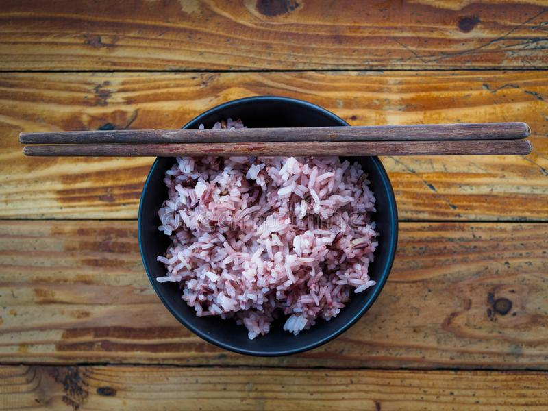 Cooked purple rice berry in bowl on rice berry grain - closeup, stock photography