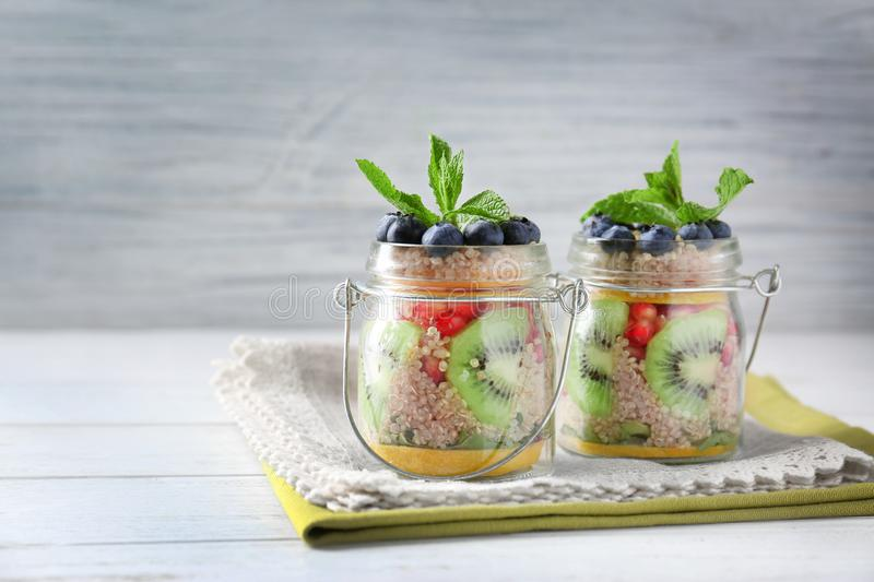 Cooked quinoa served with fresh fruits and berries. In glass jars on grey background stock images