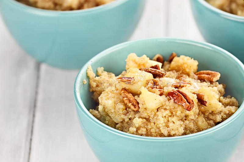 Cooked Quinoa. Three bowls of cooked quinoa with pecans, apples, and maple syrup with shallow depth of field royalty free stock photography
