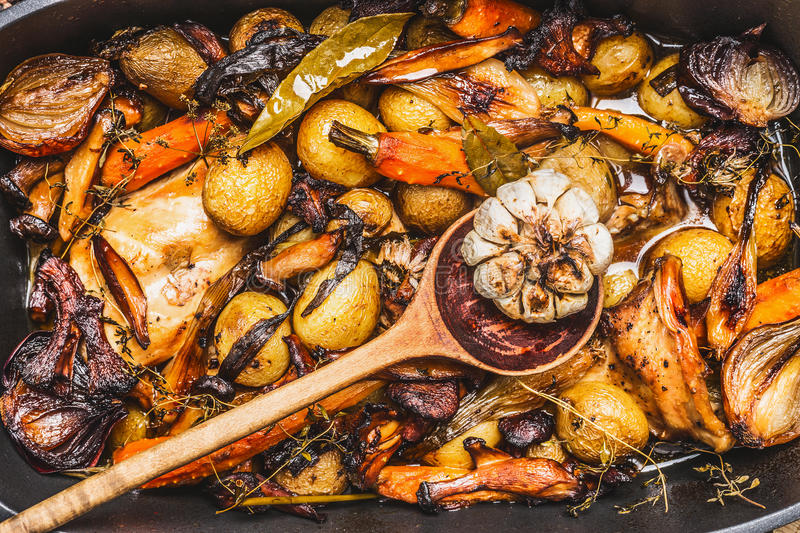 Cooked rabbit stew with forest mushrooms , roasted vegetables of season and rustic wooden spoon. Top view, close up royalty free stock photos