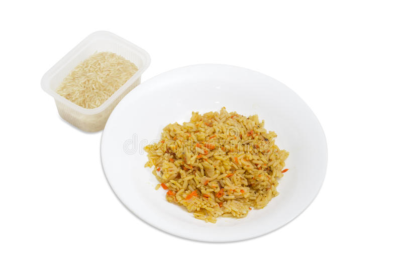Cooked rice on dish and uncooked rice in plastic container royalty free stock photo