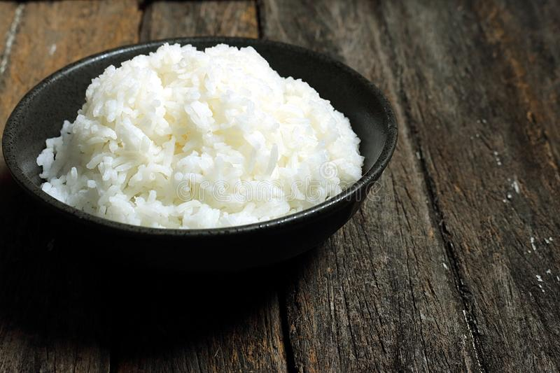 The cooked rice. Is placed in a black bowl. The backdrop is a wooden board stock photos