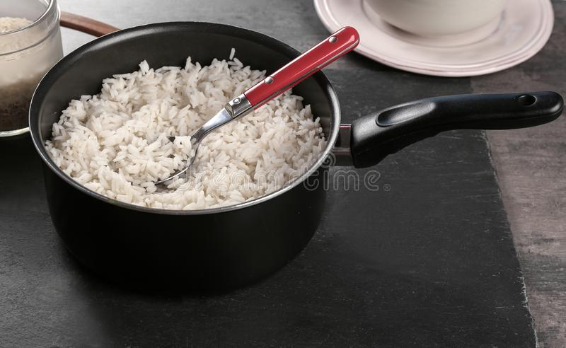 Cooked rice in saucepan with spoon. On slate board stock photos