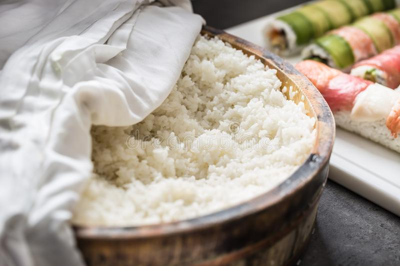 Cooked rice in a typical Japanese wooden vessel hangiri. Pile of rice before ready to prepare sushi.  royalty free stock images