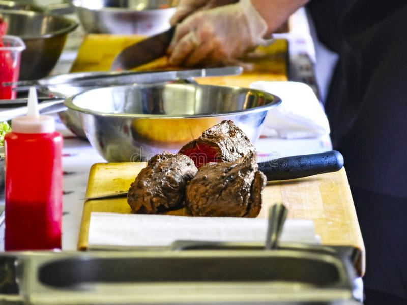 Cooked Roast Beef On a Cutting Board. Cooking Master Class, Workshop with People Learning How to Cook Around the Table royalty free stock images