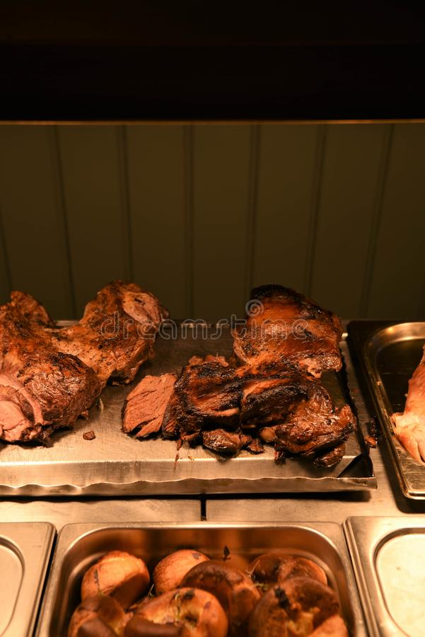 Cooked roast lamb and mutton joints of meat. Food of cooked roasted dinner or lunch in a restaurant kitchen. With whole joints of leg of lamb and braised mutton stock photo