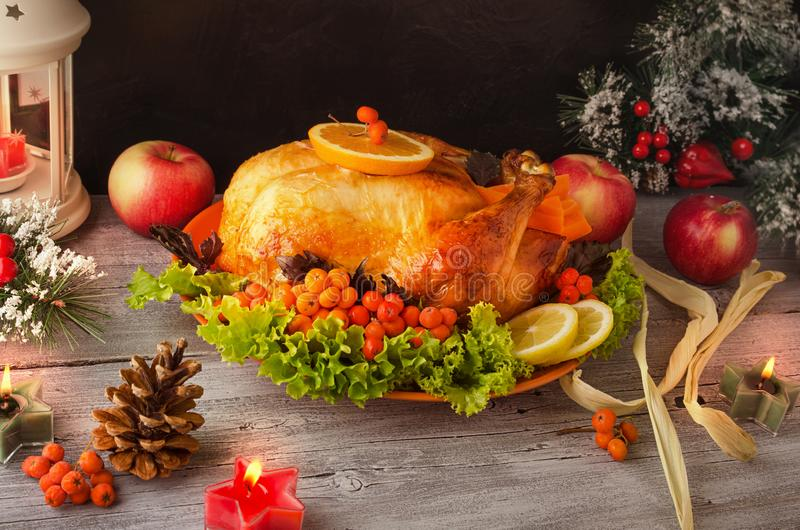 Cooked roasted Turkey with berries, vegetables and apples on wooden table background with black backdrop. stock photos