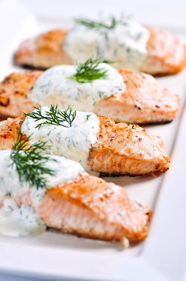 Cooked salmon. Fillets with dill sauce on white plate royalty free stock photography