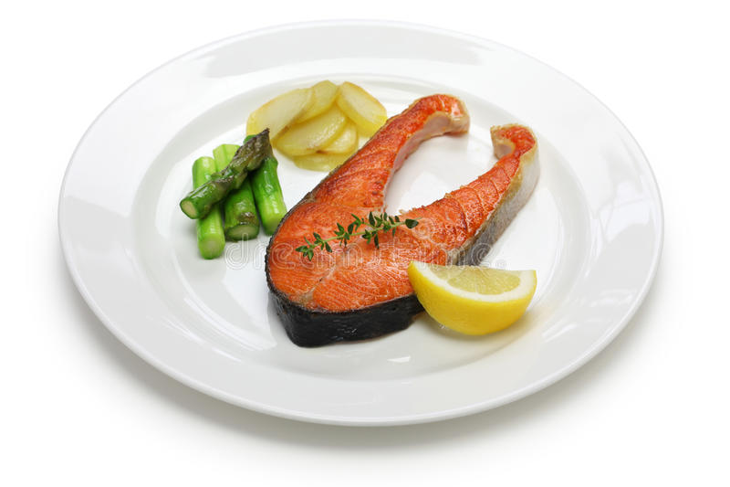 Cooked salmon steak. On white dish stock images